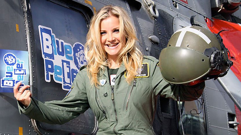 Blue Peter presenter Helen Skelton in uniform next to a Royal Navy Sea King helicopter.