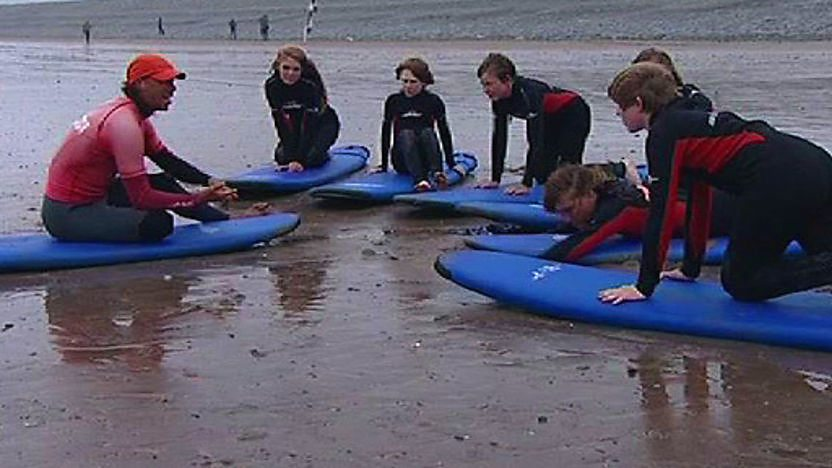 A group of children on the beach being taught to surf