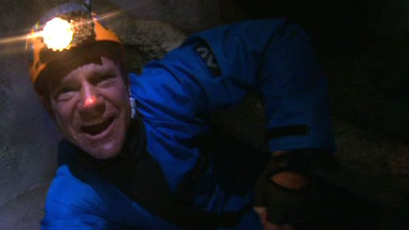 Steve Backshall wriggling through a very narrow cave