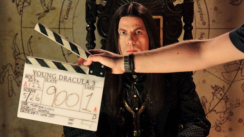 Count Dracula with a clapper board in front of his face.