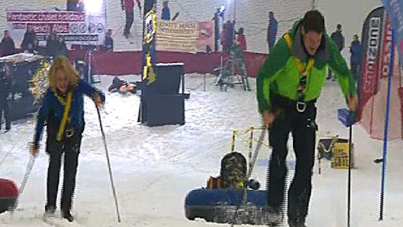 Steve Backshall racing Ann Daniels up a snow slope on skis