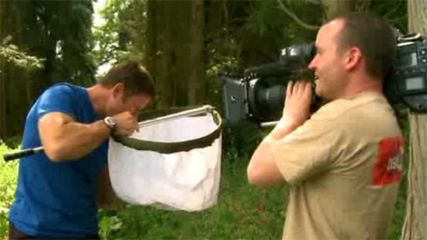 Steve Backshall looking in a massive net whilst a cameraman films him