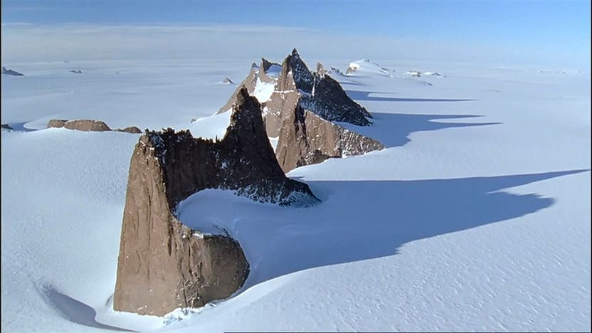 Rocky peaks, standing up and out from thick snow in the antarctic.