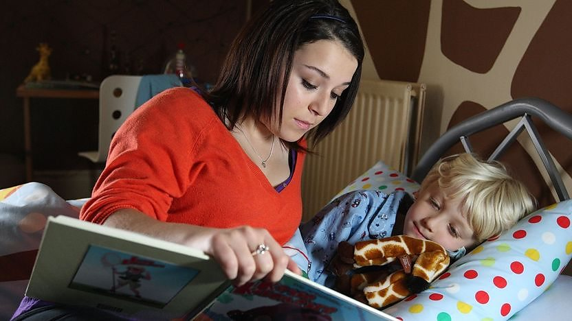 tracy reading to young child in bed