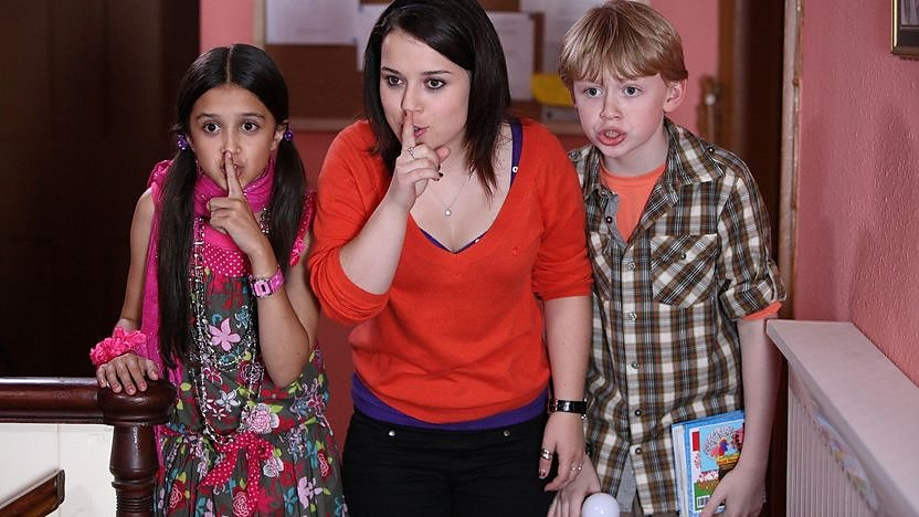 three children putting finger to mouth to signal keeping quiet