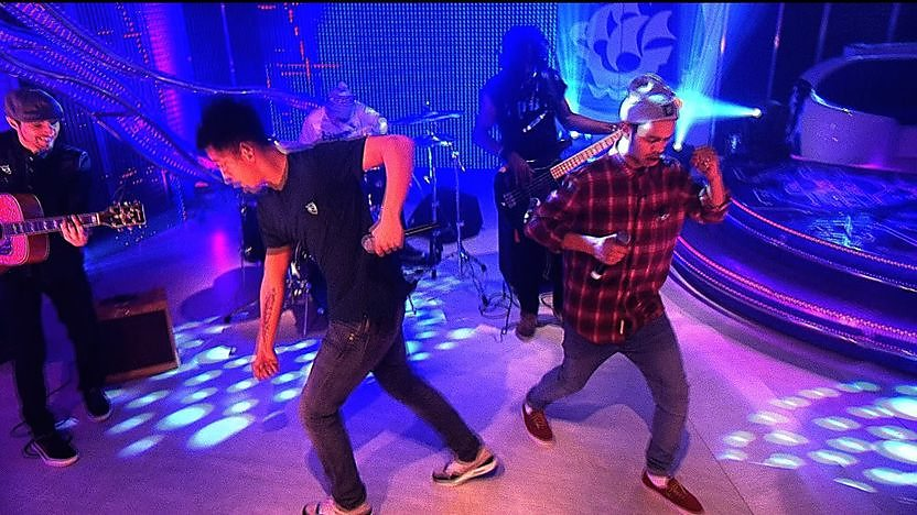 Rizzle kicks dancing in the Blue Peter studio with their band in the background.