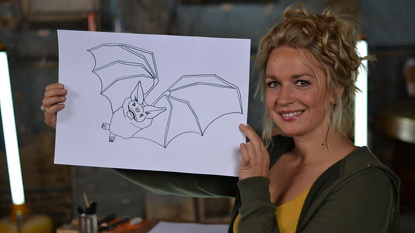 Nicola holding a drawing of a bat.