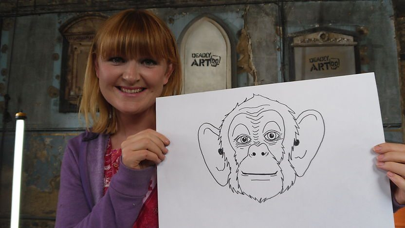 Image of Jo holding a drawing of a chimpanzee.
