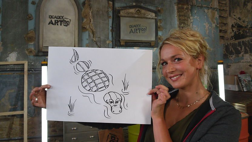 Nicola holding a drawing of a crocodile.