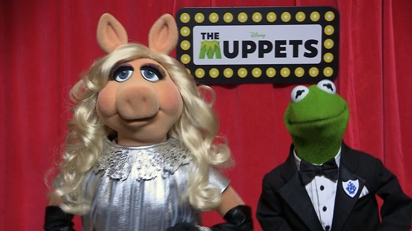 Kermit the frog and Miss Piggy the Muppets on a red background.