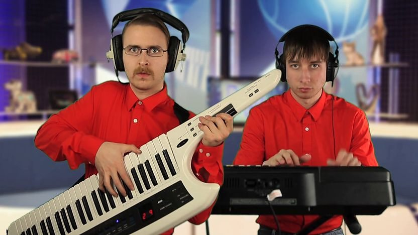 Brett Domino playing Key-tar in a red shirt next to his sidekick steve playing the keyboard super imposed into the Blue Peter studio.