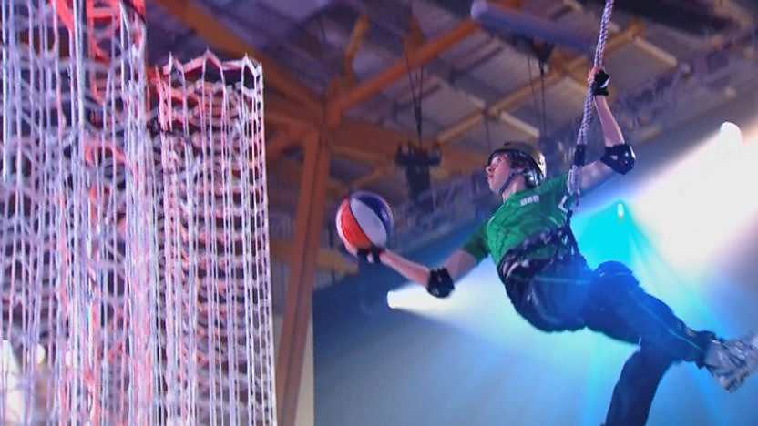 A contestant dunking a basketball into a net.