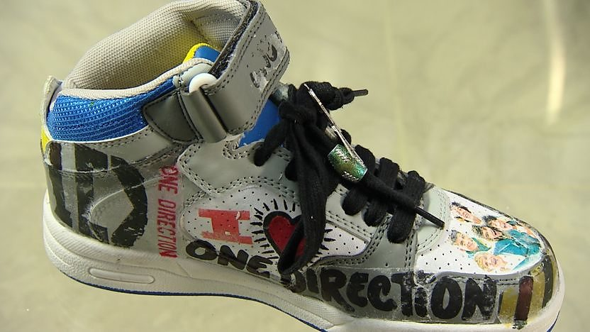 A white trainer that has been customised with One Direction images.