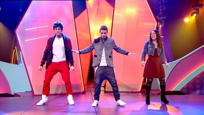 Aidan Davis, Dani Harmer and Tyger Drew-Honey on stage dancing.