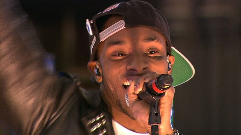 Rapper Angel holding a mocrophone to his mouth and singing. Wearing a black baseball cap backwards.