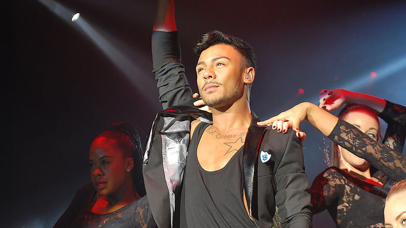 Marcus Collins performing in a red blazer wearing a blue peter badge.