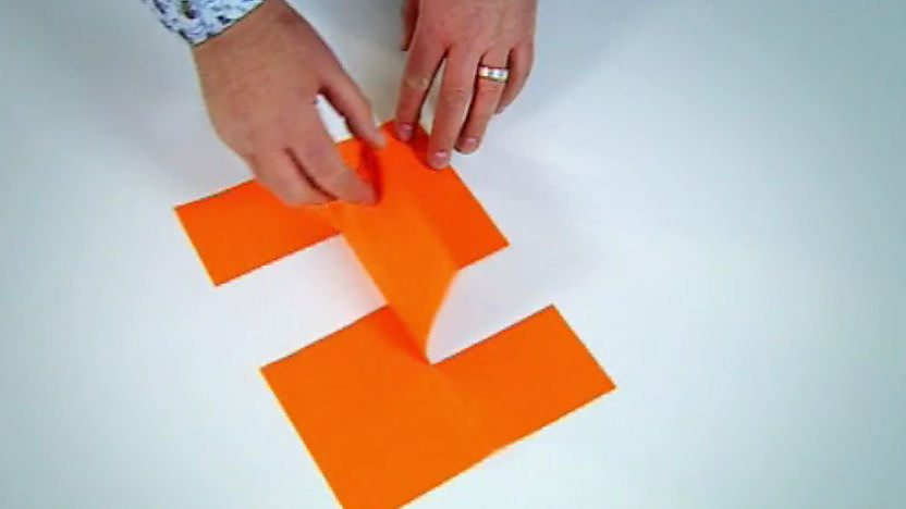 An impossible shape made from orange paper.