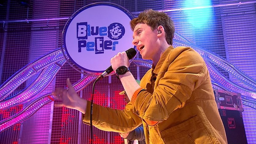 Conor Maynard performing in the Blue Peter studio wearing an orange jacket.