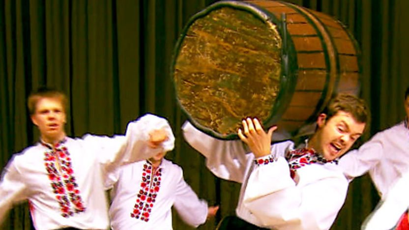Barney Harwood holding a barrel as he cossack dances on Blue Peter