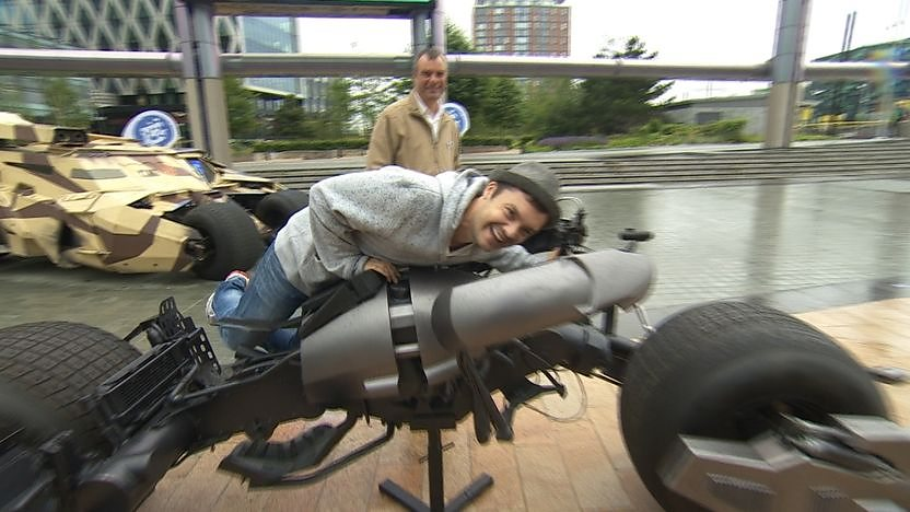 Barney Harwood sitting on the Batpod motorbike from The Dark Knight Rises