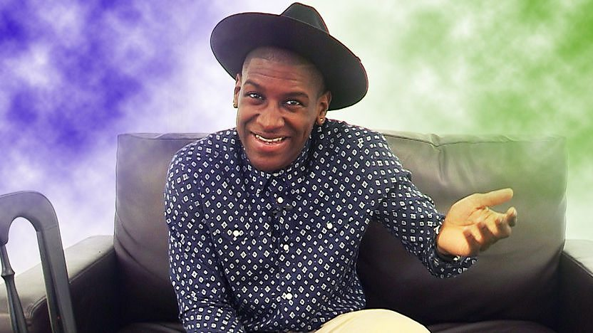 Labrinth sat on a sofa backstage at G Fest with a purple cloud and a breen cloud either side, representing CBBC Music&#39;s Silly Question or Serious Question Challenge.