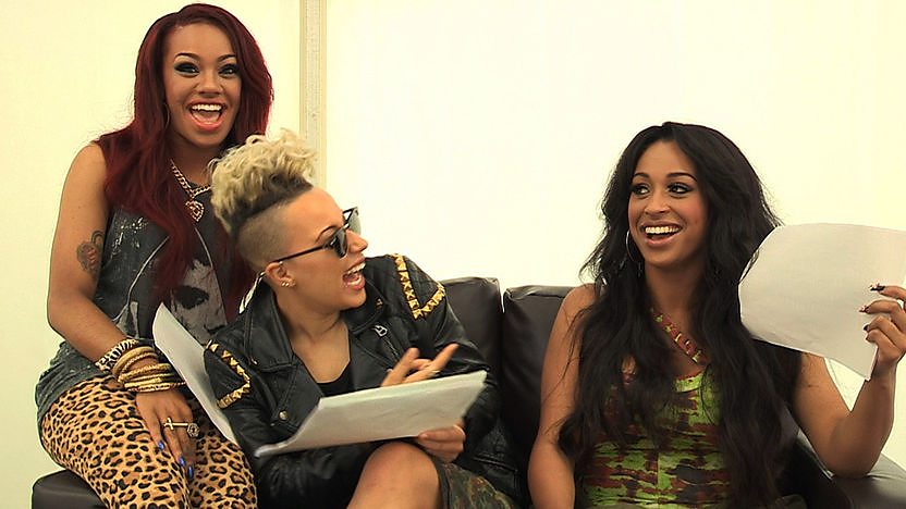 Stooshe laughing on a sofa.