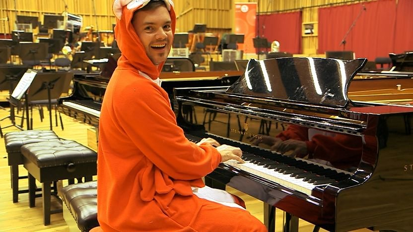 Barney Harwood playing a piano.