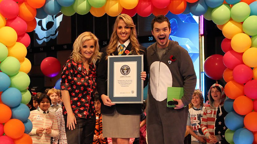 Helen, Barney and a representative from Guinness World Records in front of some balloons.