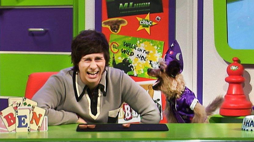 Hacker T Dog and Ben Hanlin laughing in the CBBC Office, hacker is wearing a wizards outfit.