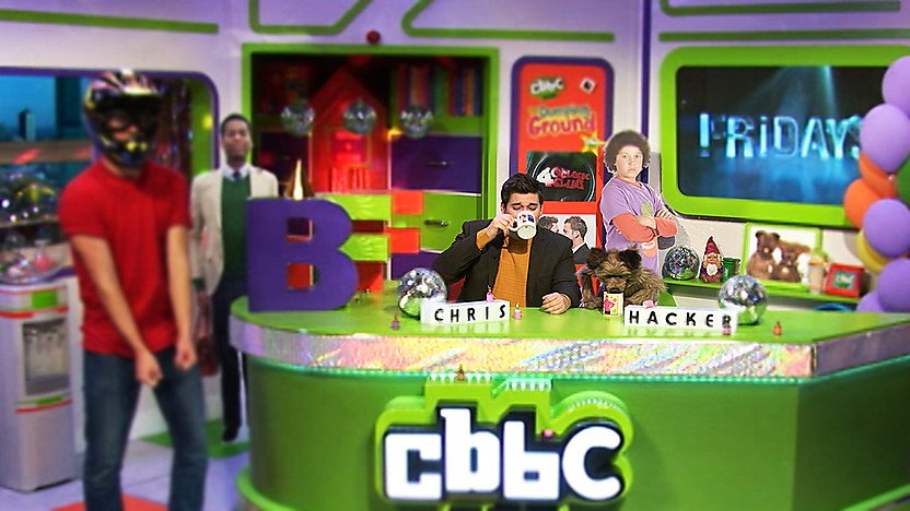 Chris Johnson and Hacker T Dog in the CBBC Office drinking a cup of tea while a man in a motorcycle helmet is stood to the left of the desk.