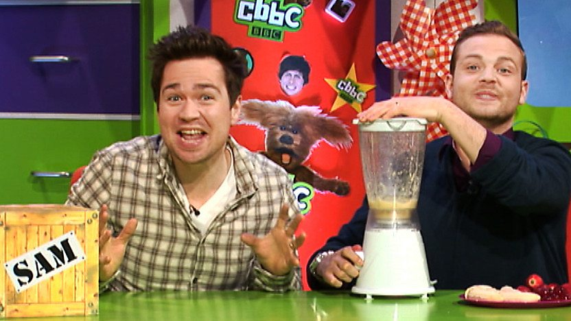 Sam Nixon pulling a funny face while Mark Rhodes blends a mixture in a blender in the CBBC Office.