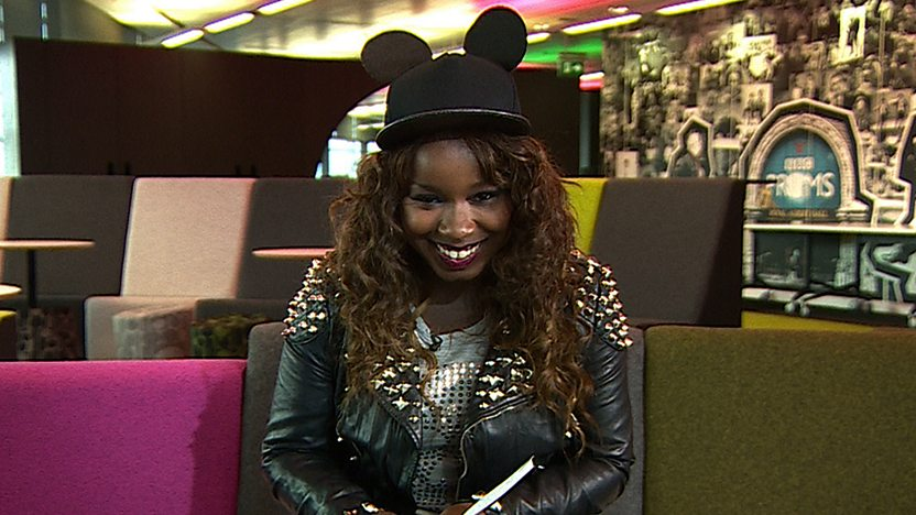 Misha B sitting on sofa looking at camera