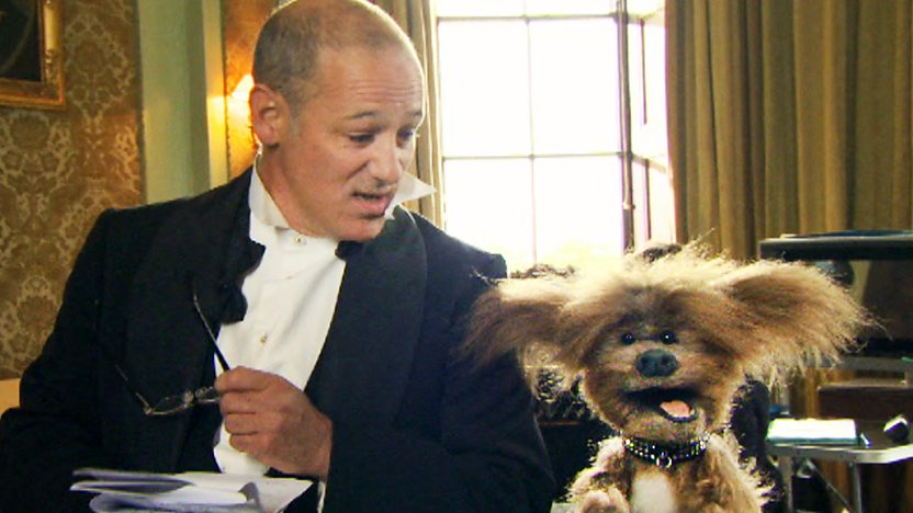 Mike Milligan from the Dumping Ground dressed up in a tuxedo next to Dodge T Dog from the CBBC Office.