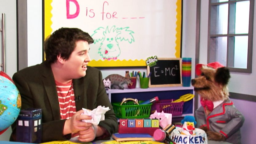 Hacker T Dog and CBBC Presenter Chris Johnson in a classroom.