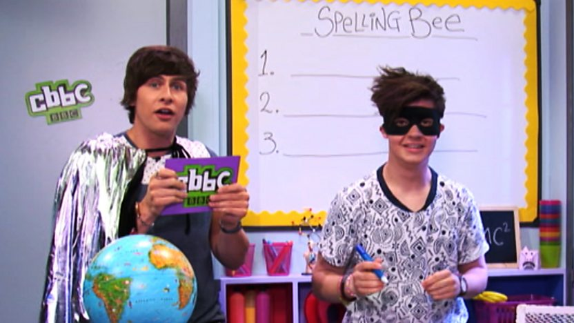 Ben and Cel in the CBBC Office classroom, Ben is wearing a silver cape and Cel is wearing a Zorro style mask.