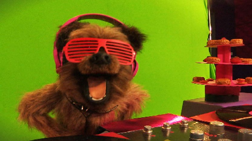 Hacker T Dog wearing rave glasses and headphones in front of a green screen.