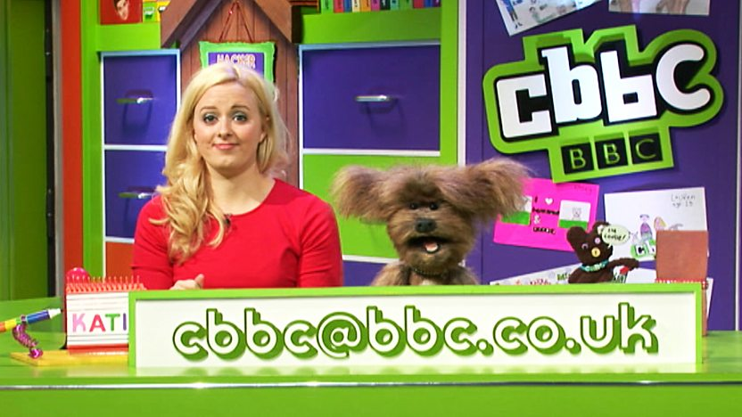 Dodge T Dog and Katie Thistleton in the CBBC Office with the CBBC Email: cbbc@bbc.co.uk in front of them.
