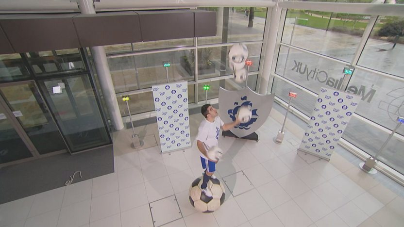Juggling genius juggling footballs on a giant football