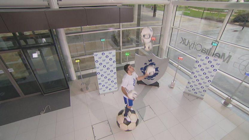 Juggling genius juggling footballs on a giant football