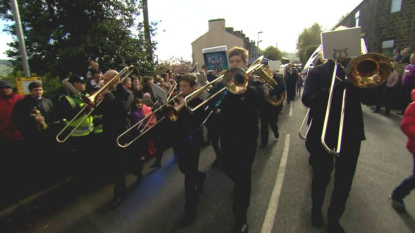 Barney playing the trombone with a brass band