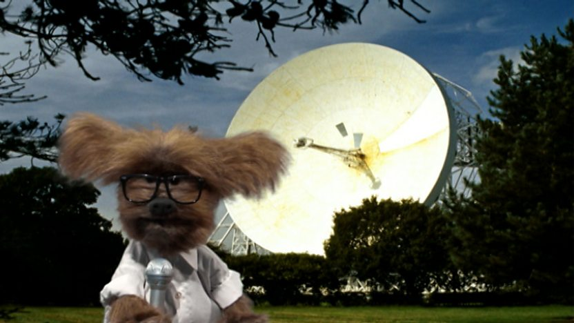 Dodge dressed as a reporter next to a satellite dish