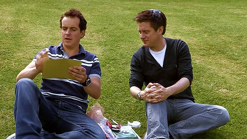 Dick and Dom sit together in a grass field