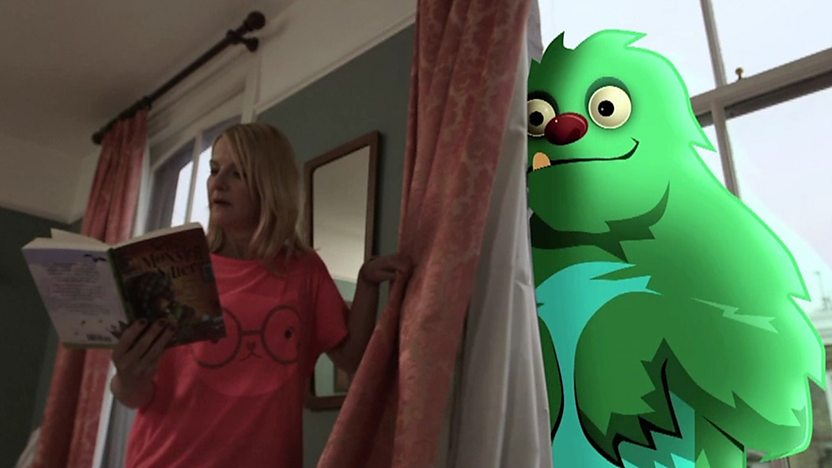 Sarah Hadland reading a book next to a green animated monster