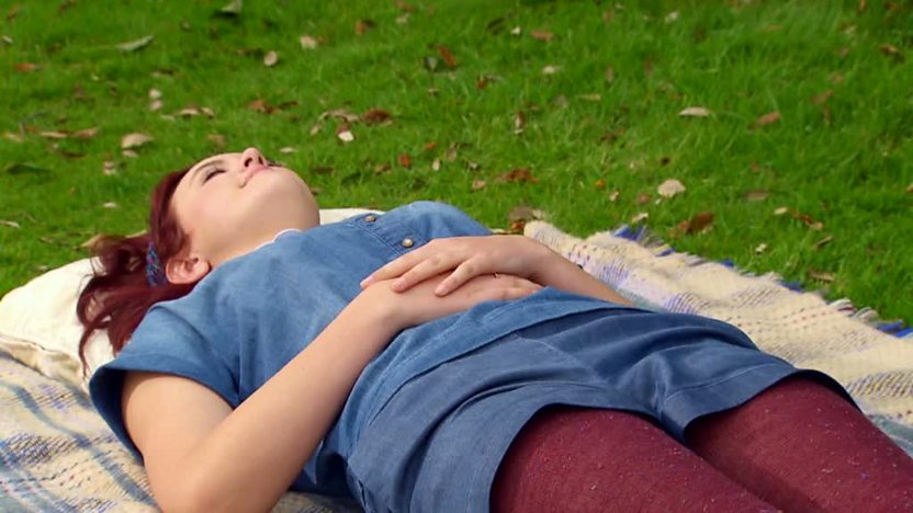 Ashleigh, from 'Britain's Got Talent', lying on the grass in a park.