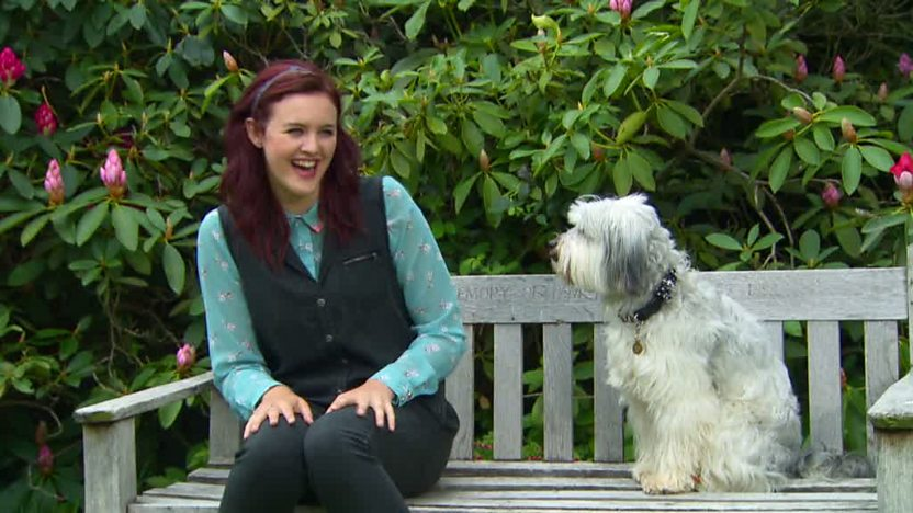 Ashleigh is sitting on a park bench with Pudsey trying to make him laugh.