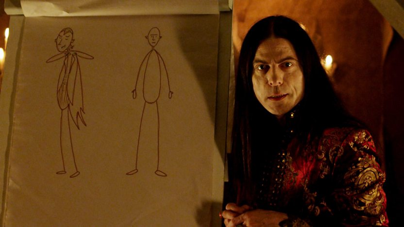 The Count from Young Dracula, next to a flipchart with drawings of a vampire and a human.