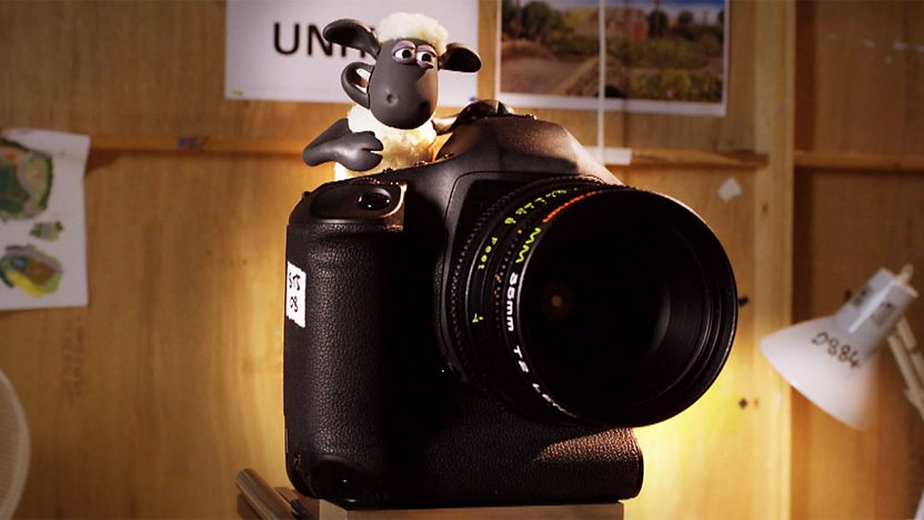 A Shaun the Sheep model behind a camera.