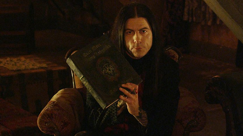 The Count from Young Dracula, holding a large old book.