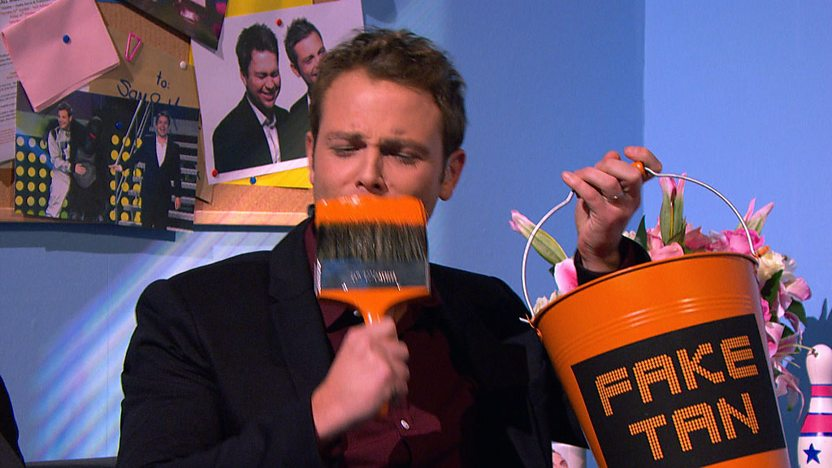 Mark holding a paintbrush to his face and holding a bucket marked 'fake tan'.