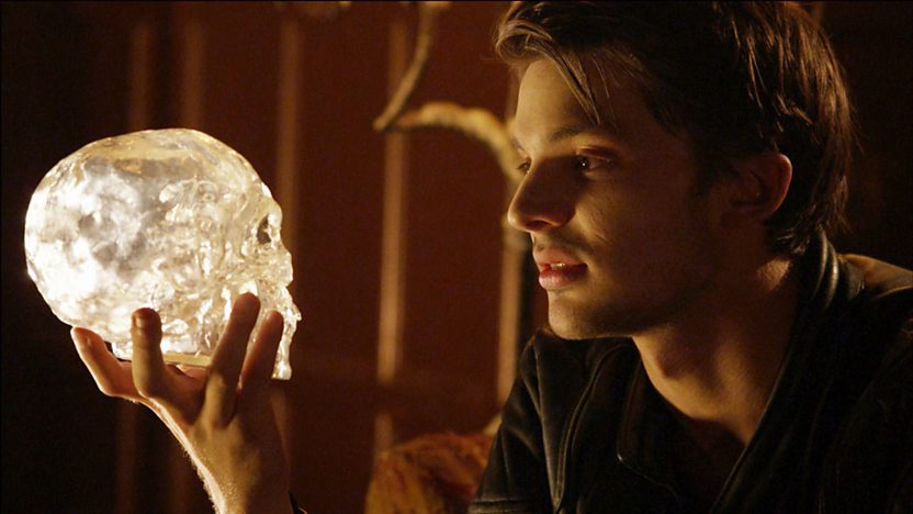 Malik from Young Dracula, holding a crystal skull.